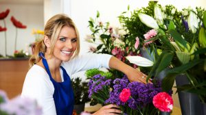 Image of smiling female florist working at flower shop