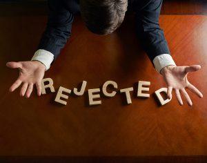 Word Rejected made of wooden block letters and devastated middle aged caucasian man in a black suit sitting at the table, top view composition with dramatic lighting